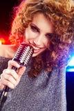 Kvinnaholdingmikrofon Arkivbilder