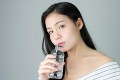 Kvinnahudskönhet och hälsa, dricksvatten från en ren flaska Huden är slät och härlig arkivbild