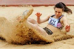 kvinnaidrottsman nenlandning i sandlängdhopp Arkivbilder