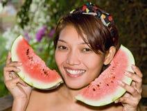 Kvinnainnehav en bevattnamelon arkivfoton