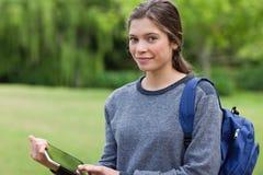 Kvinnainnehav en tabletPC fördriver anseende i en parkera Arkivbild