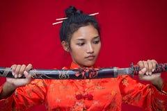 Kvinnainnehav ett svärd Royaltyfri Foto