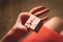 Kvinnainnehav i hennes hand en mycket liten rosa gåvaask ovanför hennes K Arkivfoton