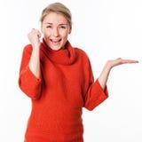Kvinnainnehav något på den tomma handen att framlägga produkten arkivbilder