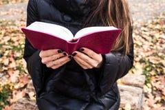 Kvinnainnehav och läsningbibel Royaltyfria Bilder