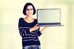 Kvinnainnehav och visningskärm av den 17 tum bärbara datorn Royaltyfri Foto