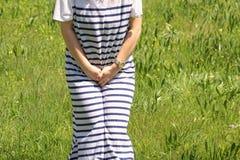 Kvinnainnehav själv som ett behov att urinera royaltyfri fotografi
