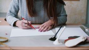 Kvinnainnehavblyertspennan, sammanträde på tabellen och teckningen skissar på papper Radering i översikt Lämnad glidare, främre s arkivfilmer