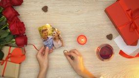 Kvinnainnehavförlovningsring och brännande lyckligt parfoto, förälskelsepass, magi stock video