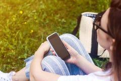 Kvinnainnehavmobiltelefon med den mörka skärmen i hennes hand Gr?sbakgrund, solstr?lar fotografering för bildbyråer