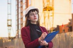 Kvinnainnehavritningar, skrivplatta Le arkitekten i hjälm på byggnad royaltyfria foton