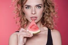 Kvinnainnehavstycke av den nya vattenmelon som isoleras på rosa färger Royaltyfri Foto