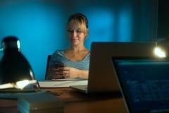 Kvinnainreformgivare Texting Phone Working sent på natten Fotografering för Bildbyråer