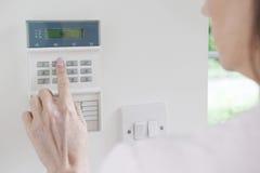 Kvinnainställningskontrollbord på system för hem- säkerhet Arkivbild