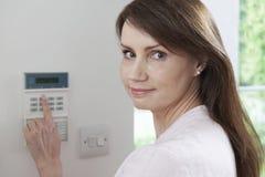 Kvinnainställningskontrollbord på system för hem- säkerhet arkivfoton