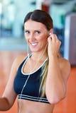Kvinnainställningsmusik på den smarta telefonen som sätter hörlurar för övning Arkivbilder