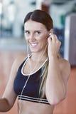 Kvinnainställningsmusik på den smarta telefonen som sätter hörlurar för övning Fotografering för Bildbyråer