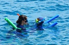 Kvinnainstruktören undervisar lilla flickan hur till att snorkla dyk arkivbilder