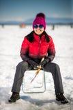 Kvinnais-fiske i vintern arkivfoto