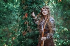 Kvinnajägare med en pilbåge i hand i skogamasonen Fotografering för Bildbyråer