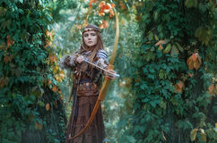 Kvinnajägare med en pilbåge i handen som tar syfte på hans rov i skogamasonen Royaltyfria Bilder