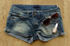 Kvinnajeanskortslutningar, spikar polermedel och solglasögon Royaltyfri Fotografi