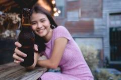 Kvinnajubel som dricker ölflaskan Ung flicka som klirrar rostat brödalc royaltyfri foto