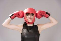 Kvinnakämpe som bär en huvudgavel och röda boxninghandskar royaltyfri bild