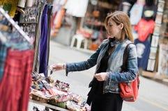 Kvinnaköpande i en gatamarknad Arkivbilder