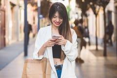 kvinnaköpande och prata med mobilen Royaltyfria Bilder