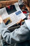 Kvinnaköpande som läser New York Times om Collin Farrell royaltyfri bild
