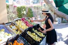 Kvinnaköpandefrukter och grönsaker på den utomhus- marknaden för bönder Stående av shopping för ung kvinna för sund livsstil royaltyfria bilder