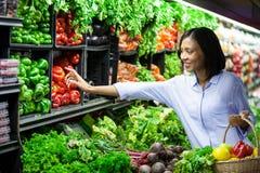 Kvinnaköpandegrönsaker i organiskt avsnitt royaltyfria bilder