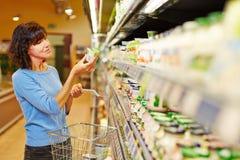 Kvinnaköpandeyoghurt i supermarket royaltyfri foto
