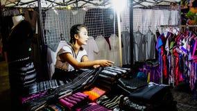Kvinnaköpmannen säljer färgrika modelltyger på Sangkhlabu Arkivfoto