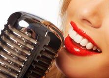 Kvinnakanter med den retro mikrofonen Royaltyfria Bilder