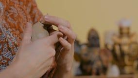 Kvinnakeramiker som g?r den keramiska souvenirencentmyntet att vissla i krukmakeriseminarium lager videofilmer