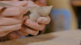 Kvinnakeramiker som g?r den keramiska souvenirencentmyntet att vissla i krukmakeriseminarium stock video