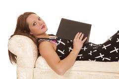 Kvinnaklänningkors lägger den lästa boken ner Arkivbilder