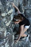 Kvinnaklättring upp ett berg arkivfoto