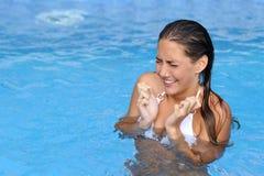 Kvinnaklagomål i ett kallt vatten av en simbassäng Arkivbild
