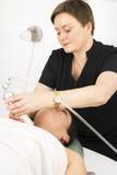 Kvinnaklienten får framsidabantningbehandling på skönhetkliniken royaltyfri bild