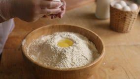 Kvinnakocken bryter ett ägg i mjöl stock video