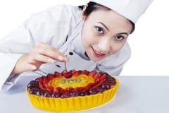 Kvinnakocken dekorerar en kaka Arkivfoton