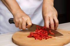 Kvinnakocken förbereder röda peppar i köket Fotografering för Bildbyråer