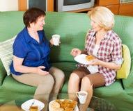 Kvinnakollegor som dricker coffe och talar under kaffeavbrott Arkivbild