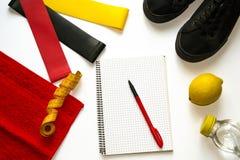 Kvinnakonditionsammansättning med elastiska gummiexpanders, gymnastikskor, anteckningsbok, panna, nya frukter, citron, flaska med royaltyfri bild