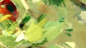 Kvinnakonstnär som blandar olika färger för olje- målarfärg på en palett arkivfilmer