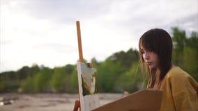 Kvinnakonstnär som målar en-pleinluft lager videofilmer
