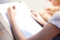 Kvinnakonstnärdanande skissar något Arkivfoto